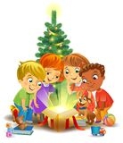 Christmas miracle - kids opening a magic gift beside a Christmas tree Stock Photo