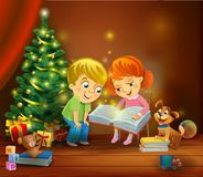 Christmas miracle - kids reading the book beside a Christmas tree Stock Photo