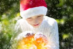 Christmas miracle. Little excited boy in santa`s hat waiting for christmas miracle to happen enjoying snowy weather, holiday concept Royalty Free Stock Image
