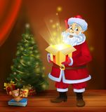Christmas miracle - Santa Claus holding a box with a magic gift beside a Christmas tree Stock Images