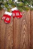 Christmas mitten decor and snow fir tree over wooden background Royalty Free Stock Photos