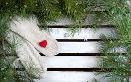 Christmas mitten decor and snow fir tree over wooden background with copy space Stock Image