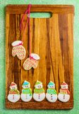 Christmas mittens on the cutting board winter selebration background. Christmas mittens on the cutting board with snowmans winter selebration background cookies Royalty Free Stock Photo