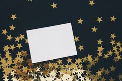 Christmas mock up greeting card on black background with gold stars confetti. Invitation, paper. Place for text flat lay Royalty Free Stock Image