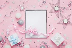 Christmas mockup with frame, holiday balls, gift boxes and sequins on stylish pink table top view. Fashion festive background. royalty free stock photography