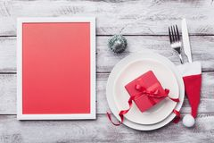Christmas mockup for holiday table setting. Picture frame, gift, fir tree, white plate and silverware on rustic table top view. stock images