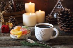 Christmas mode: coffee, colorful candies and burning candles. New Year composition: cup of coffee and pine cones, burning candles and colorful candies Stock Photos