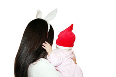 Christmas Mom and Baby. A young women with bunny ears holding her baby with red Santas hat from behind isolated on white Royalty Free Stock Image