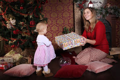Christmas Mom gives daughter gift stock photos