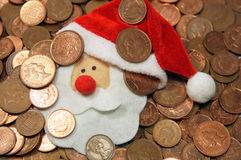 Christmas Money. A Santa face is amongst the coins Stock Image