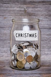 Christmas, money jar with coins on wood table Royalty Free Stock Photo