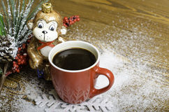 Christmas monkey near a red coffee cup. Stock Photo