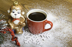 Christmas monkey near a red coffee cup. Stock Photos