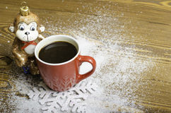 Christmas monkey near a red coffee cup. Royalty Free Stock Photography