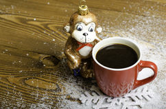 Christmas monkey near a red coffee cup. Royalty Free Stock Images