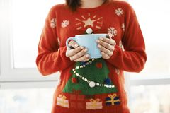 Christmas mood is in air. Cropped shot of woman at home, wearing funny christmas sweater with tree, holding huge cup. With coffee and standing over window Stock Photo