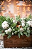 Christmas mood. Beautiful festive arrangement of fresh spruce in a rustic wooden box. Bokeh hearts of Garland lights on. Background. Decorated with Bells, balls royalty free stock image