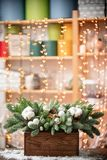 Christmas mood. Beautiful festive arrangement of fresh spruce in a rustic wooden box. Bokeh hearts of Garland lights on. Background. Decorated with Bells, balls royalty free stock photography
