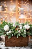 Christmas mood. Beautiful festive arrangement of fresh spruce in a rustic wooden box. Bokeh hearts of Garland lights on. Background. Decorated with Bells, balls stock photography