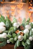 Christmas mood. Beautiful festive arrangement of fresh spruce in a rustic wooden box. Bokeh hearts of Garland lights on. Background. Decorated with Bells, balls stock photos
