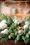 Christmas mood. Beautiful festive arrangement of fresh spruce in a rustic wooden box. Bokeh hearts of Garland lights on. Background. Decorated with Bells, balls royalty free stock images