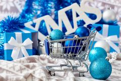 Christmas mood. Christmas decoration with ornaments and small trolley in blue Stock Image