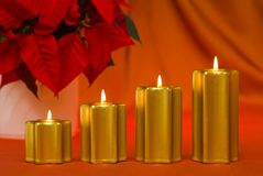 Christmas mood with golden candles. Four golden candles in a row and poinsettia with warm colored background royalty free stock photos