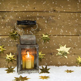 Christmas mood: old rustic latern on a snowy background. Royalty Free Stock Photo