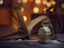 Christmas mood. Opened book of fairy tales and Christmas decorations on a wooden table. stock photos
