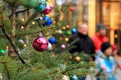 Christmas mood while shopping. Christmas balls on the tree in a shopping street stock photos