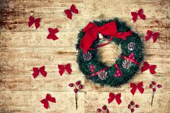 Christmas mood top view. Christmas wreath and red ribbons on wooden background. toned image Stock Photo