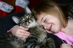 Christmas Morning. Adorable little girl snuggling with her pet cat. Christmas stockings hanging in the background stock photography