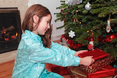 Christmas Morning. A girl opening Christmas presents under a Christmas tree with a log fire in the background Stock Photo