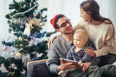 Family gathered around a Christmas tree, using a tablet. Christmas morning, cheerful family sitting in the living room having fun with the digital tablet that Royalty Free Stock Photography