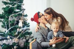Family gathered around a Christmas tree, using a tablet. Christmas morning, cheerful family sitting in the living room having fun with the digital tablet that Stock Image