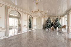 Christmas morning. classic luxurious apartments with decorated christmas tree. Living hall large mirror, chair, high. Windows, columns and stucco royalty free stock photos