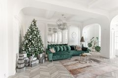 Christmas morning. classic luxurious apartments with decorated christmas tree. Living hall large mirror, green sofa. Christmas morning. classic luxurious stock photos