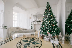 Christmas morning. classic luxury apartments with a white fireplace, decorated tree, bright sofa, large windows Royalty Free Stock Images