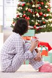 Christmas morning coffee. Woman in pyjama sitting on floor on Christmas morning, drinking coffee, looking at tree and gifts Royalty Free Stock Photography