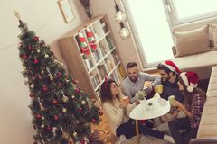 Christmas morning coffee. Young friends sitting on the living room floor next to a Christmas tree on a Christmas morning, drinking coffee. Focus on the couple Royalty Free Stock Images