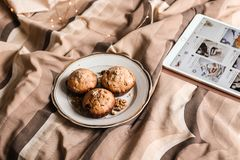 Delicious fresh walnut muffins on a plate in bed. royalty free stock photos