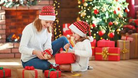 Christmas morning. family mother and daughter unpack, open gift Stock Images
