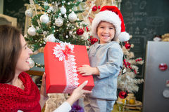 Christmas morning joy. Happy mother giving Christmas present to her cheerful little boy who is wearing Santas hat and looking at camera Royalty Free Stock Photo