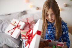 Christmas morning. Little girl looking inside of Christmas present royalty free stock photos