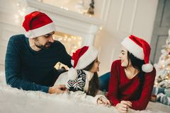 Christmas morning, Mom and dad and their little daughter together on home , Enjoing Holidays Family people royalty free stock photography