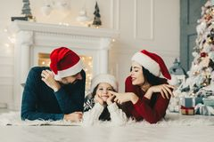 Christmas morning, Mom and dad and their little daughter together on home , Enjoing Holidays Family people royalty free stock photo