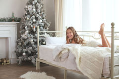 Christmas morning. Preteen child girl wake up on her bed near decorated Christmas tree in beautiful hotel room in the holiday morning Stock Photos