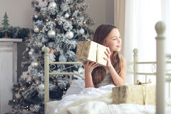 Christmas morning. Preteen child girl wake up in her bed near decorated Christmas tree in beautiful hotel room in the holiday morning, enjoing with presents Royalty Free Stock Image