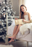 Christmas morning. Preteen child girl wake up in her bed near decorated Christmas tree in beautiful hotel room in the holiday morning, opening presents Royalty Free Stock Images