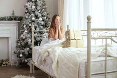 Christmas morning. Preteen child girl wake up in her bed near decorated Christmas tree in beautiful hotel room in the holiday morning, surprised with presents Royalty Free Stock Photos
